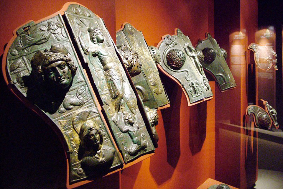 Antike Maskenhelme, Ross-Stirnen, Beinschienen und Statuetten aus Messing und Bronze sind im Gäubodenmuseum in Straubing ausgestellt.
