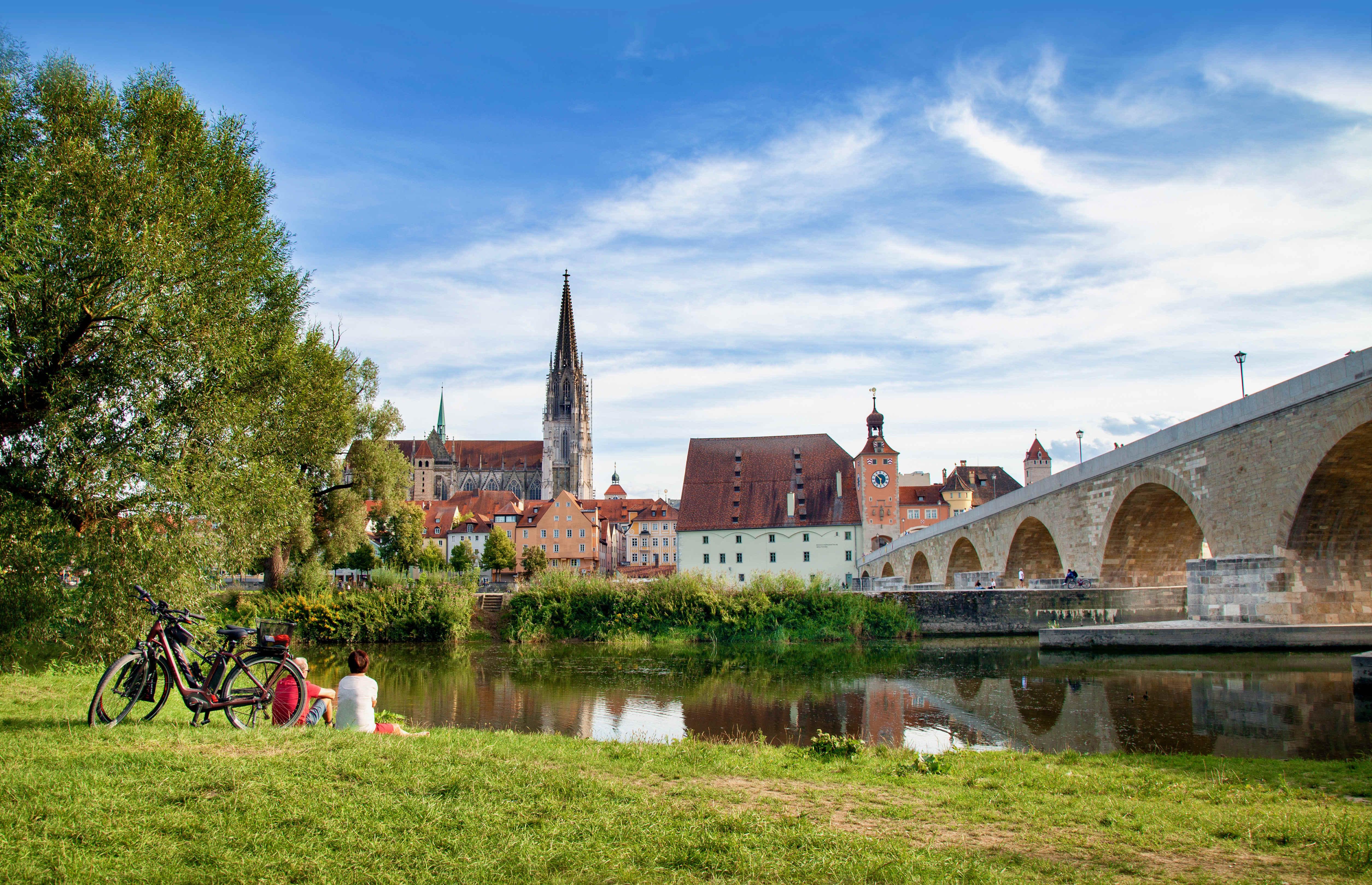 Radler an der Steinernen Brücke in Regensburg genießen den Blick über die Donau zum Dom.