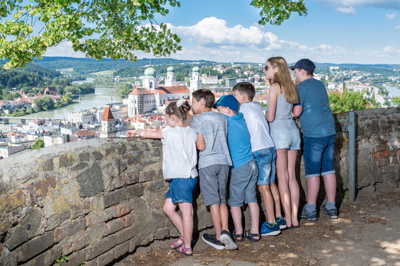 Im Schatten von alten Linden können Kinder und Erwachsene einen atemberaubenden Ausblick auf die historische Altstadt von Passau genießen.